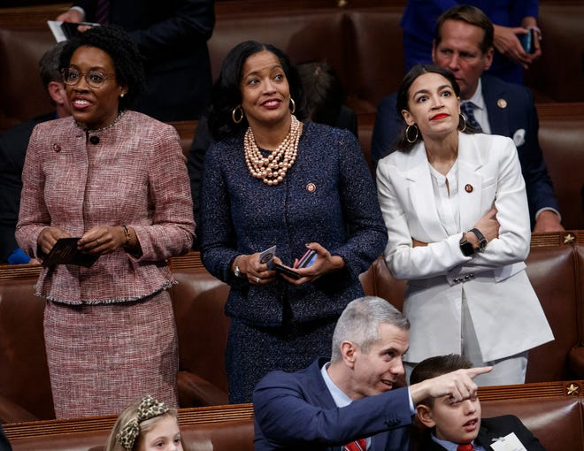 Democratic Reps. Alexandria Ocasio-Cortez (R), Jahana Hayes (C) and Lauren Underwood (L) take in the scene during the opening session of the 116th Congress.