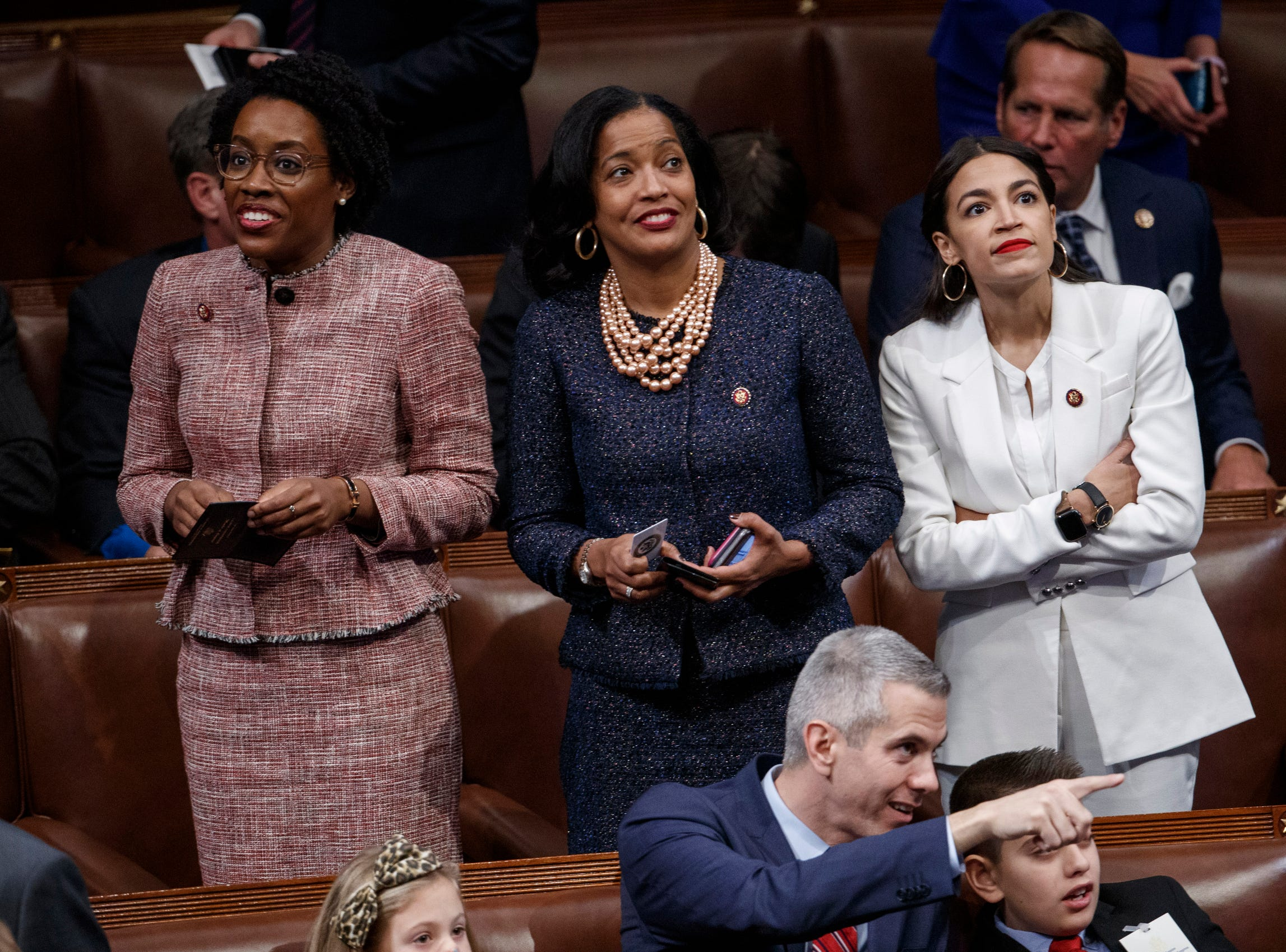 Democratic Representatives Alexandria Ocasio-Cortez (R) and Jahana Hayes (C) and Lauren Underwood (L) take in the scene during the opening session of the 116th Congress.