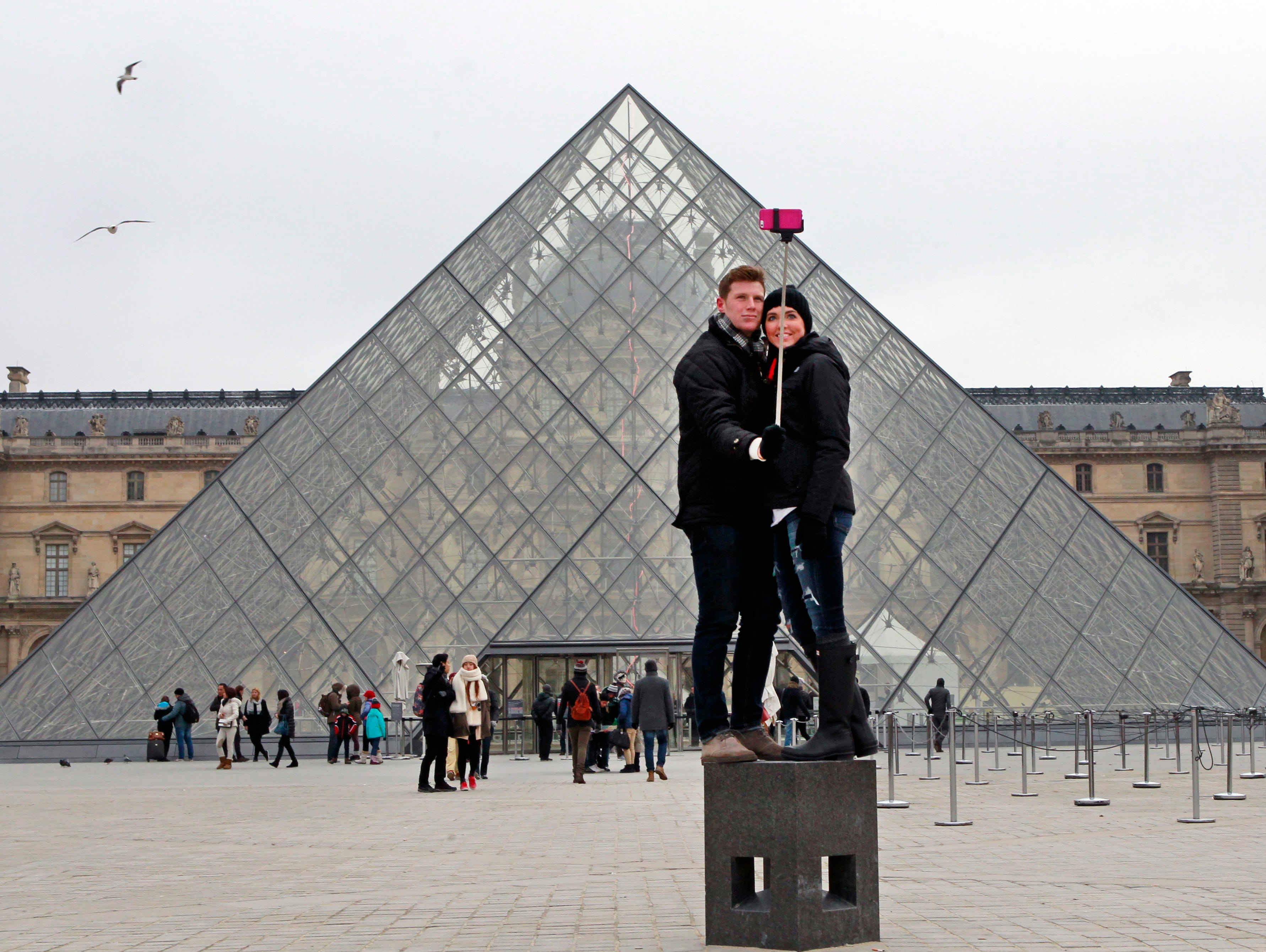 FILE - In this Tuesday, Jan. 6, 2015, Chris Baker and Jennifer Hinson from Nashville, Tennessee, use a selfie stick in front of the Louvre Pyramide in Paris. The world's most visited museum, the Louvre in Paris registered 10.2 million visitors in 2018, a record boosted by a rise of foreign tourists and pop star Beyonce's video paying tribute to the Mona Lisa and others world-famous artworks. (AP Photo/Remy de la Mauviniere, File) ORG XMIT: PAR101