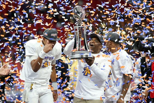 North Carolina A&T  coach Sam Washington celebrates with his players after defeating Alcorn State in the Celebration Bowl.