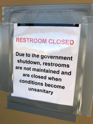 A sign on a set of toilets at Rocky Mountain National Park in Colorado tells visitors the doors are locked because there is no one to clean them during the partial government shutdown.