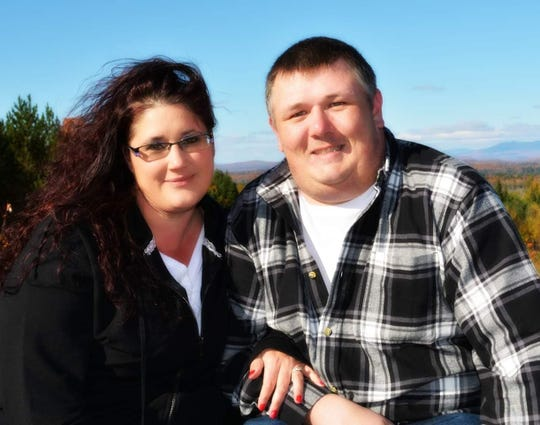 Jordan Smith and his wife, Tracey, pose in front of an overlook in Madison, Maine.