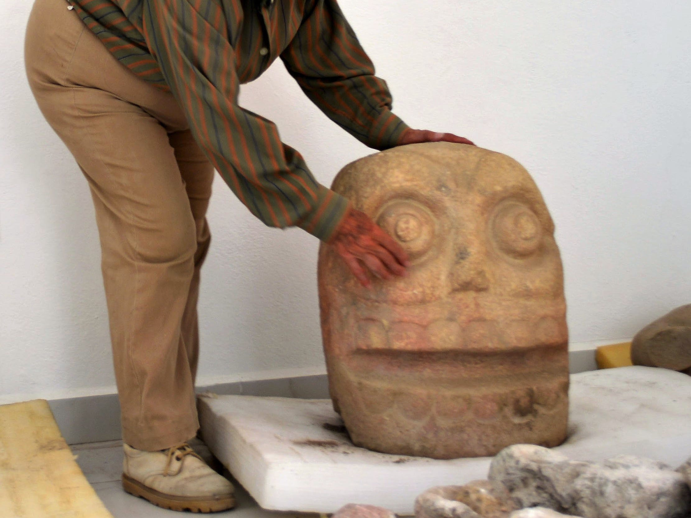Handout picture released by Mexico's National Institute of Anthropology and History (INAH) taken on October 12, 2018 showing Mexican archaeologist Noemi Castillo showing a sculpture found at the first temple recently discovered of pre-Hispanic fertility god Xipe Totec (The Flayed Lord), in the archaeological site of Ndachjian-Tehuacan, in the Mexican state of Puebla.