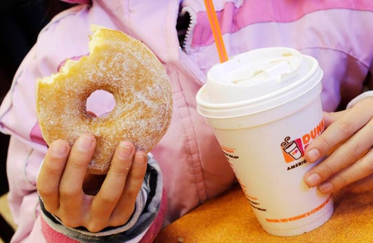 FILE- In this Feb. 14, 2013 file photo, a girl holds a beverage, served in a foam cup, and a donut at a Dunkin' Donuts in New York. The new year means no more plastic foam coffee cups, takeout containers or packing peanuts in most places in the nation's largest city. New York City's long-planned ban took effect on Tuesday, January 1, 2019. (AP Photo/Mark Lennihan, File)