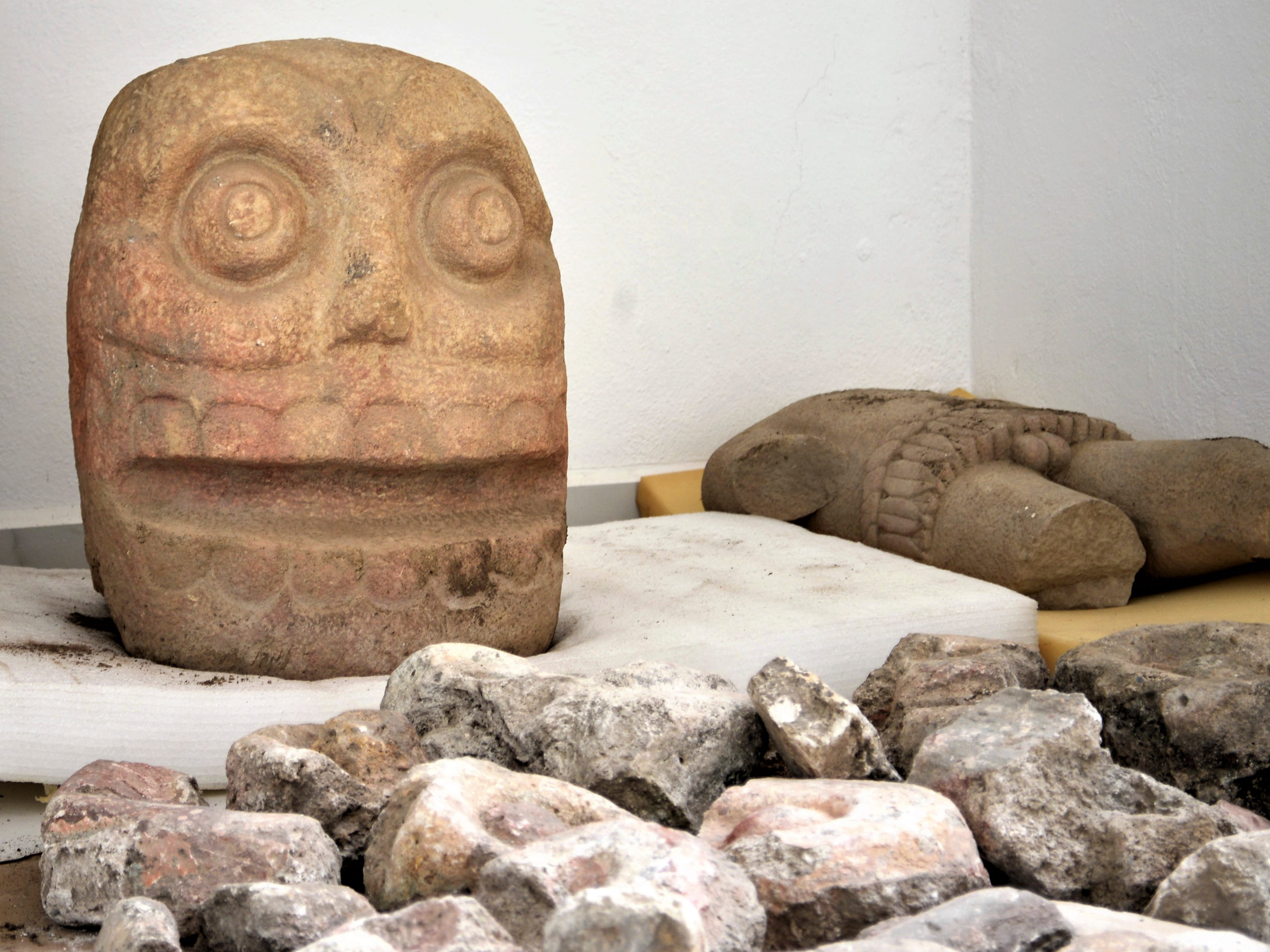 In this 2018 photo provided by Mexico's National Institute of Anthropology and History, INAH, a skull-like stone carving and a stone trunk depicting the Flayed Lord, a pre-Hispanic fertility god depicted as a skinned human corpse, are stored after being excavated from the Ndachjian–Tehuacan archaeological site in Tehuacan, Puebla state, where archaeologists have discovered the first temple dedicated to the deity. Although depictions of the god, Xipe Totec, had been found before in other cultures, a whole temple had never been discovered.