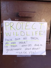 A sign on a garbage can at Rocky Mountain National Park in Colorado tells visitors to take their trash with them during the partial government shutdown.