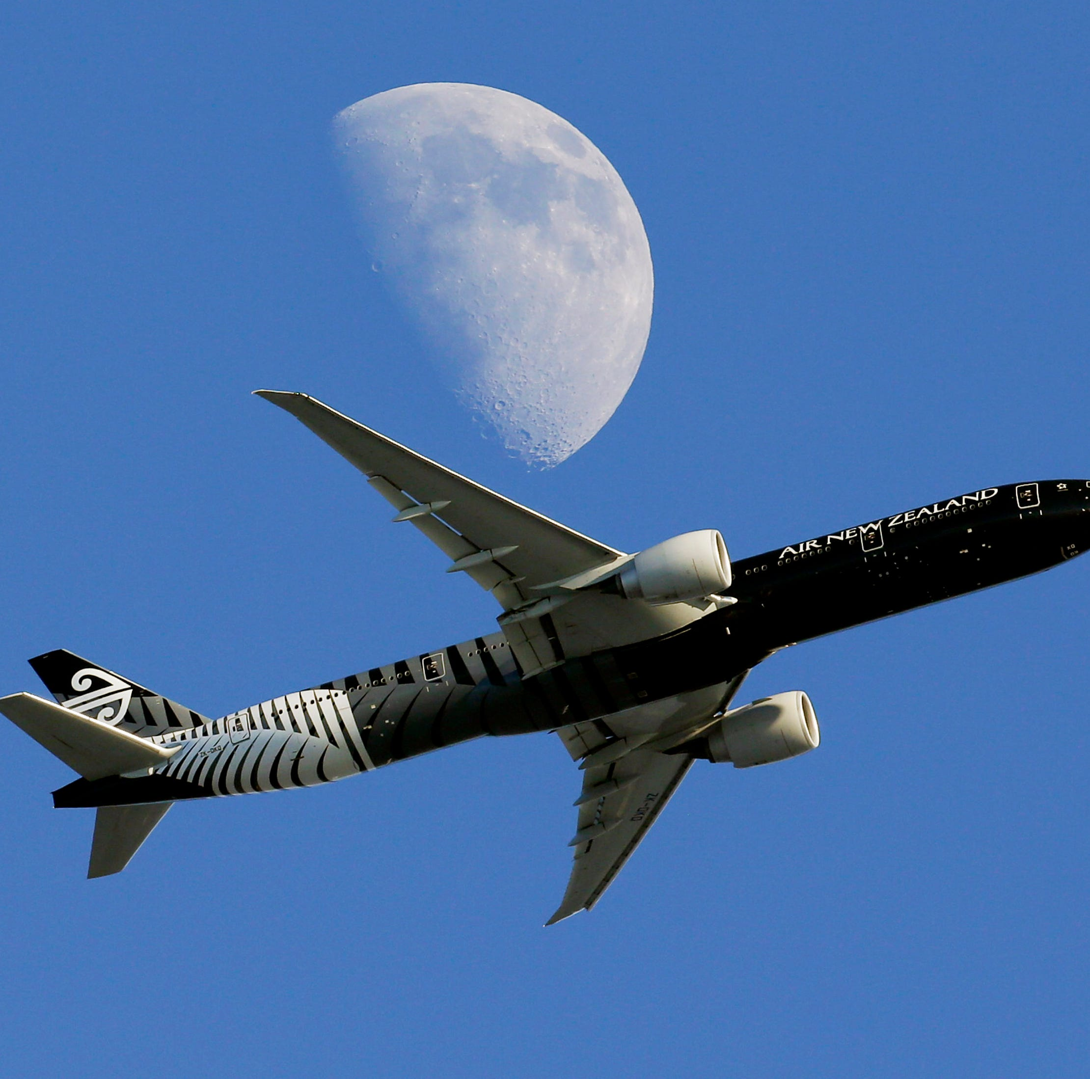 FILE - In this Aug. 23, 2015, file photo, an Air New Zealand passenger plane flies past the moon on its way to the Los Angeles International Airport from London, in Whittier, Calif. When a drone flew within meters of a landing passenger plane on March 25, 2018, Air New Zealand said reckless drone operators should be thrown in prison. Other agencies chimed in, calling such actions inexcusable and stupid. Yet The Associated Press has found that not one of them called police. Not while it was endangering the plane, nor later to try to track down the perpetrator. (AP Photo/Nick Ut, File) ORG XMIT: TKTT101