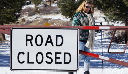 Kate McMillen, 58, walks past a road closure sign at Rocky Mountain National Park on Jan. 2, 2019. The park is largely closed and unstaffed due to the federal government closure.