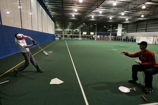 In this archived photo from 2011, a player gets batting practice and coaching at Players Choice of the Fox Cities.