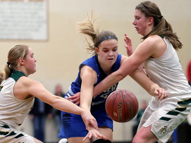 Freedom's Carly Peters, left, and Karissa Wurster, right, defend against Wrightstown's Ella Diny during a game Jan. 3 in Freedom.