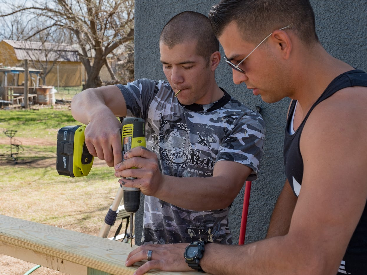 Staff Sgt. Garrett Jue and Airman 1st Class Dustin Osborne put the finishing touches on a wheelchair ramp at a March Dyess We Care Team project.