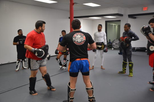 Assistant Coaches Dan Kujda (left) and Chavezz Russell demonstrate a combination of moves to a class at Mushin Academy of Martial Arts on Thursday, Jan. 3, 2019.