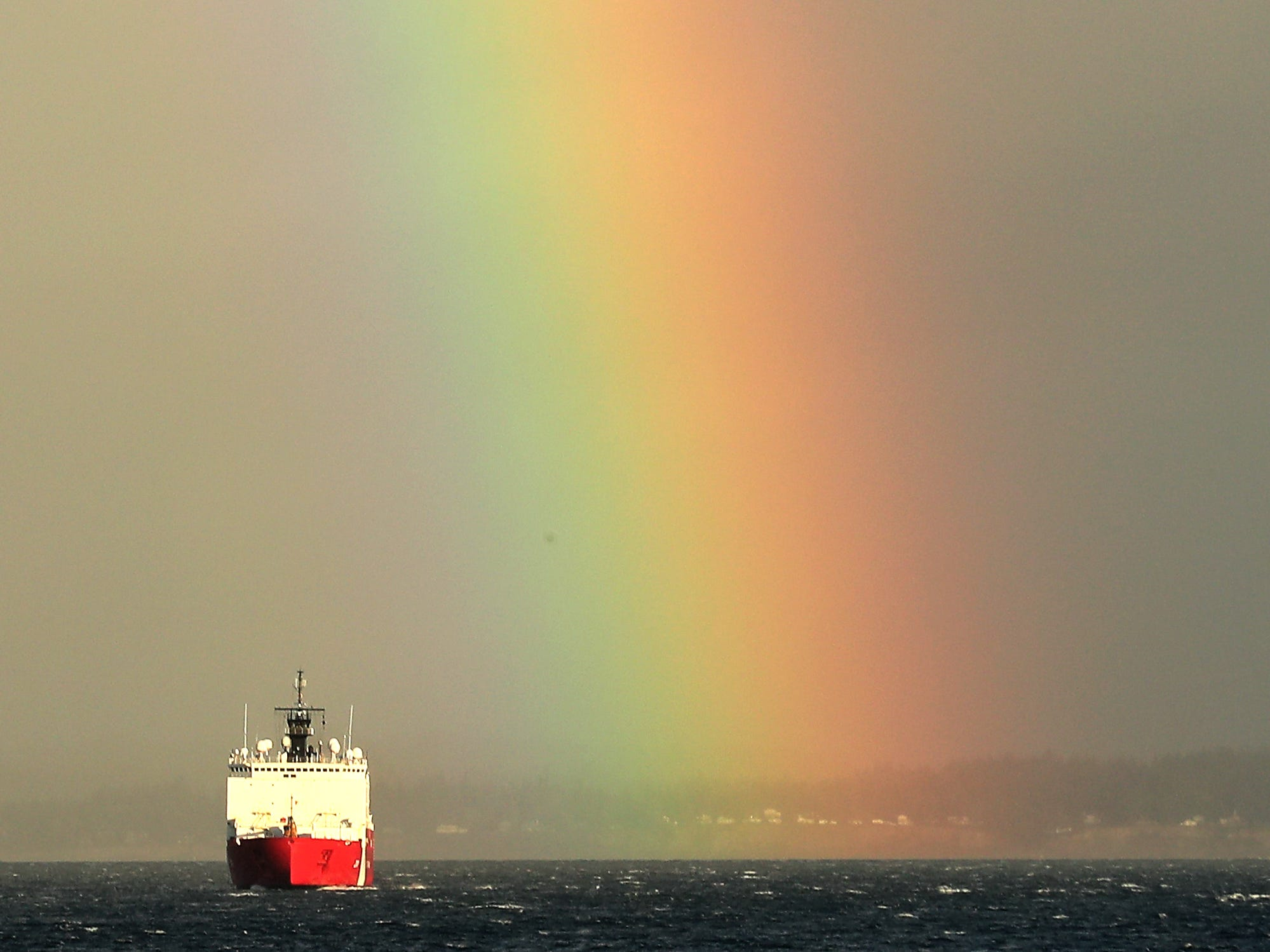 The US Coast Guard Cutter Healy moves through the choppy seas and passes the end of a rainbow as seen from M/V Puyallup between Bainbridge Island and Seattle on Friday, January 4, 2019.