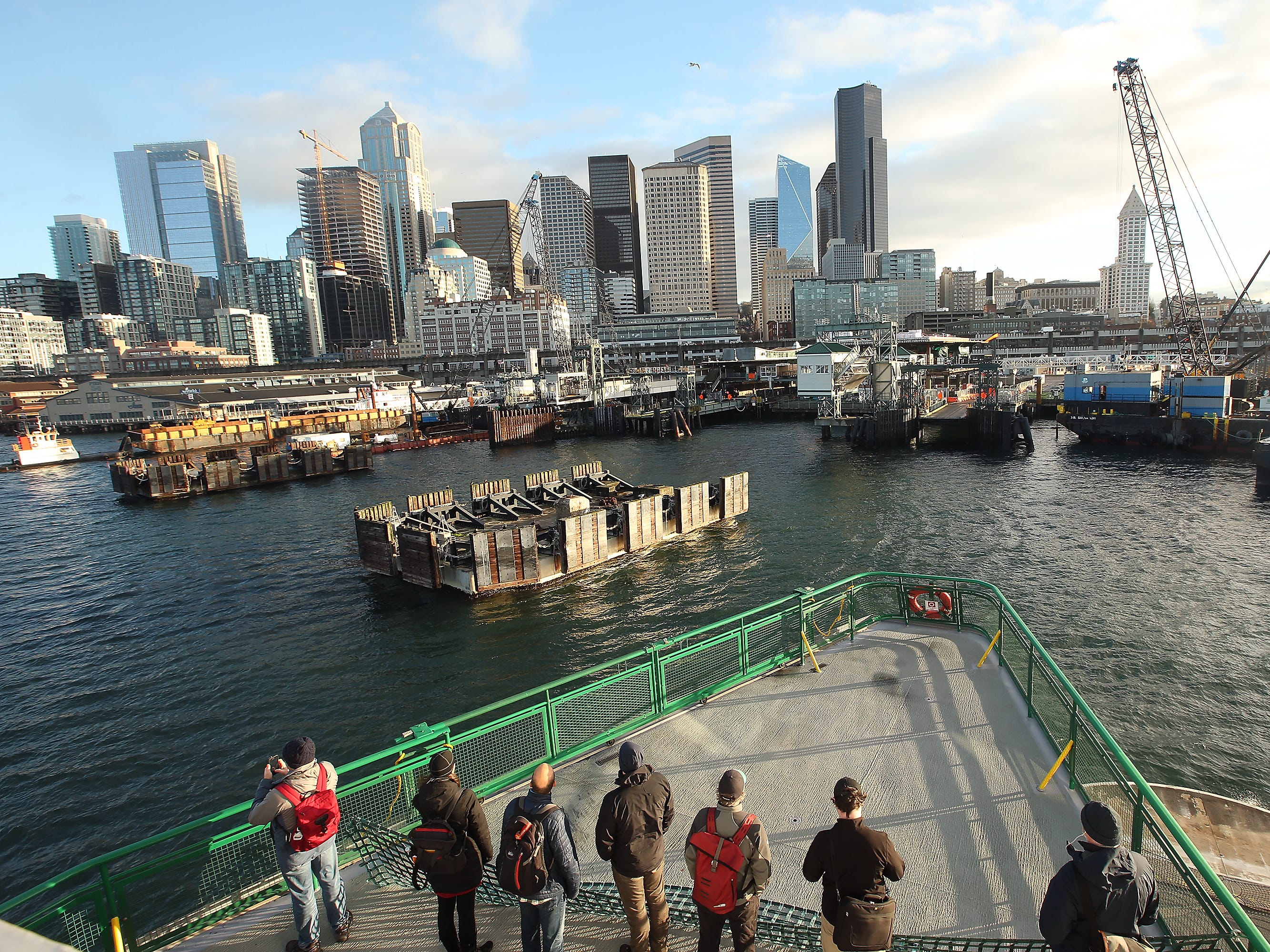 Ferry riders take in the construction and skyline view as the M/V Puyallup heads for Coleman Dock in Seattle on Friday, January 4, 2019.
