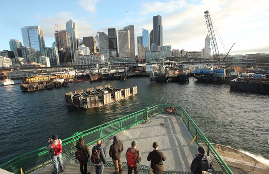 Ferry riders take in the construction and skyline view as the M/V Puyallup heads for Colman Dock in Seattle on Friday, January 4, 2019.