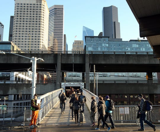 Ferry commuters head for the Coleman Dock pedestrian bridge under the Alaskan Way Viaduct in Seattle on Friday, January 4, 2019.