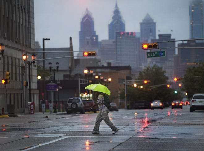 A pedestrian crosses Market Street during a heavy rainstorm in Camden. The corridor is one of three roadways slated for improvements.