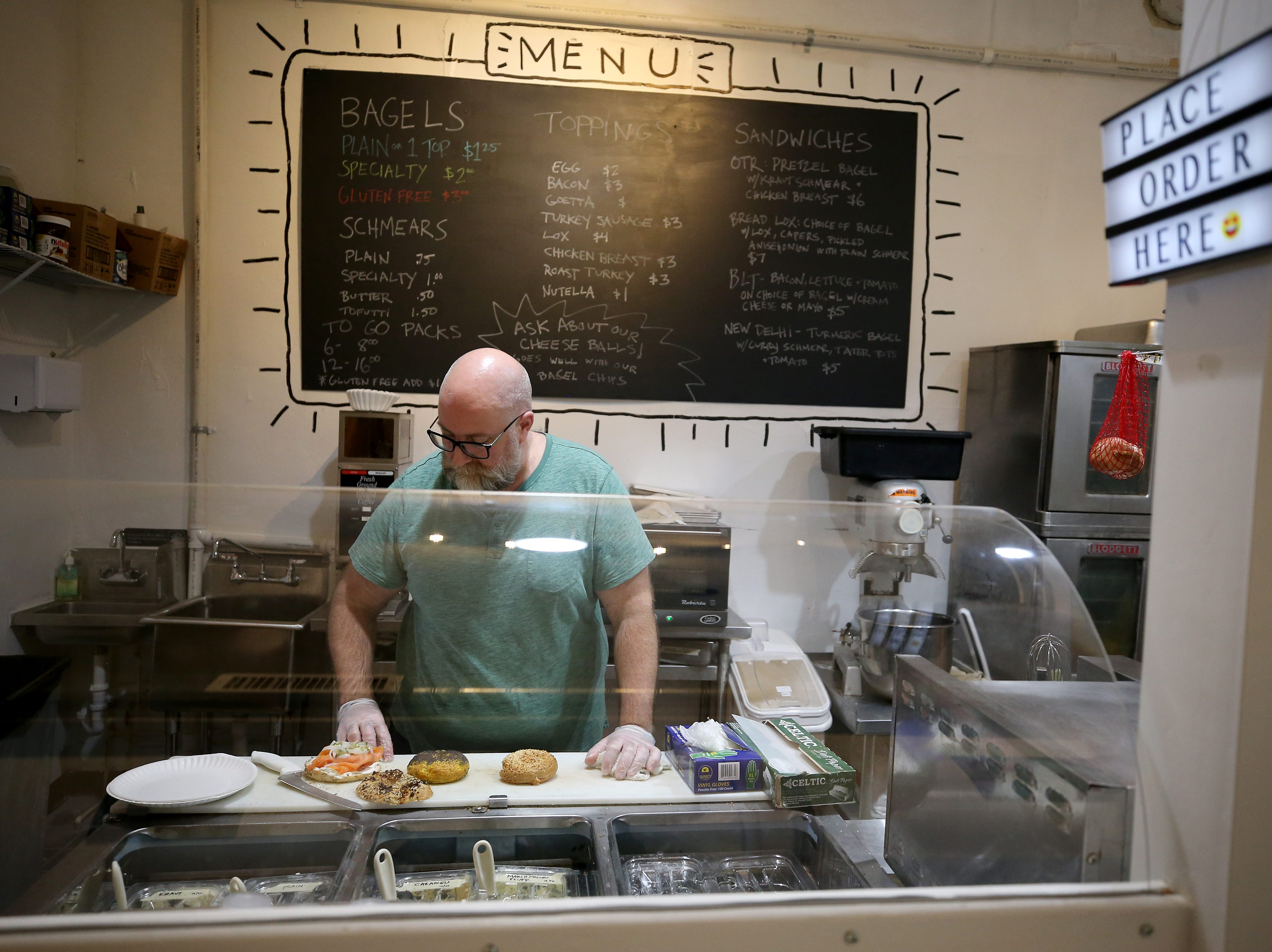 Marshall Mann, owner of OTR Bagel Bar, prepares bagels, pictured, Thursday, Jan. 3, 2019, at OTR Bagels located at Findlay Market in Cincinnati.