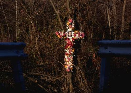 A flower cross memorial for Nancy Noga in the area where her body was found behind the Mini Mart Plaza, on Ernston Road in Sayerville.