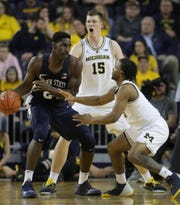Michigan's Jon Teske (15) and Zavier Simpson (3) defend Penn State's Mike Watkins, Jan. 3 at Crisler Center.