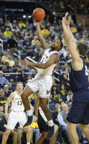 Michigan guard Zavier Simpson scores against Penn State forward John Harrar during first half action Thursday, January 3, 2019 at the Crisler Center in Ann Arbor, Mich.