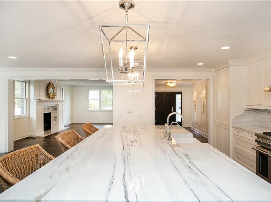 The dining room, family room, kitchen, living room, mudroom and two half bathrooms are all on the first floor. The kitchen has an oversized marble island, marble counter tops and a hidden, walk-in pantry.