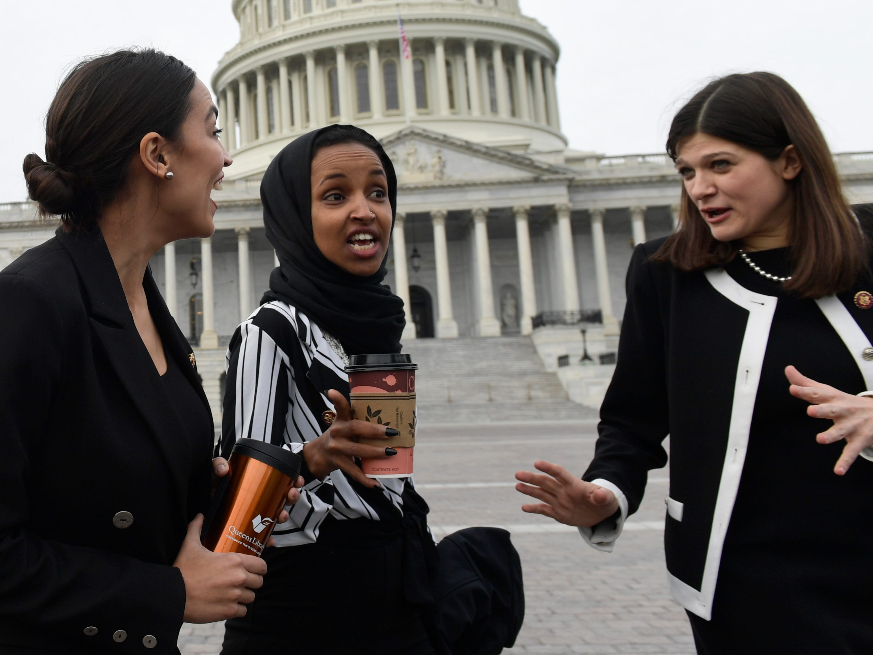 Rep. Alexandria Ocasio-Cortez, D-N.Y., left, talks with Rep. Ilhan Omar, D-Minn., center, and Rep. Haley Stevens, D-Mich., right, as they head to a group photo with the women of the 116th Congress on Capitol Hill in Washington, Friday, Jan. 4, 2019.