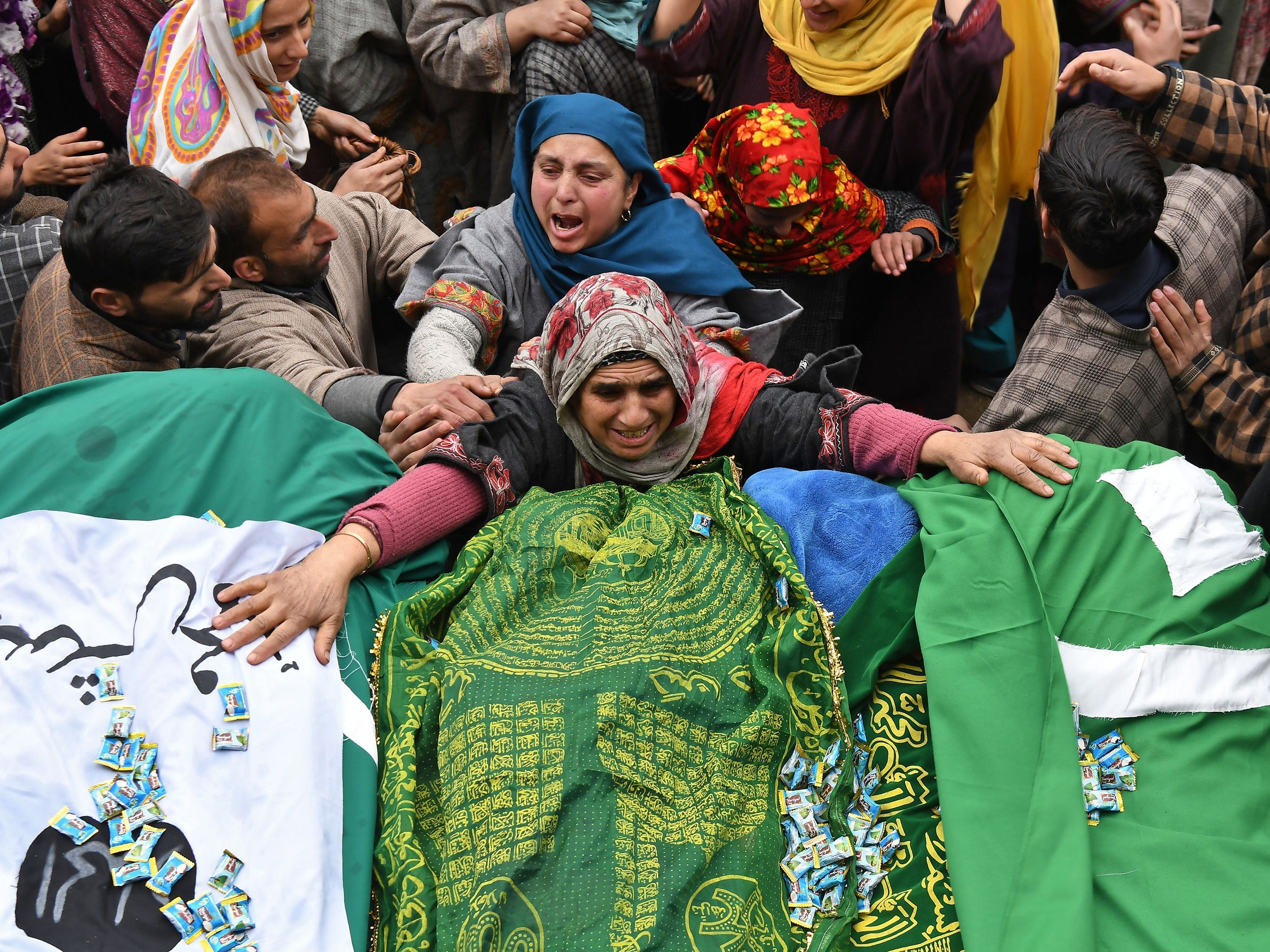 A Kashmiri woman touches the feet of two slain militants during a funeral procession in Chursoo Awantipora, in Pulwama district south of Srinagar, on Jan. 4, 2019. Three militants were killed and one Indian army soldier injured during a gun battle in Gulshanpora Tral, south of Srinagar, on Jan. 3, Indian media reports said.