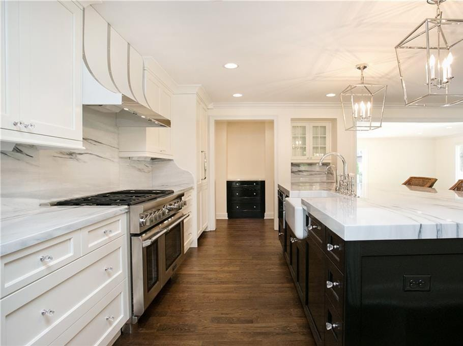 The dining room, family room, kitchen, living room, mudroom and two half bathrooms are all located on the first floor. The kitchen has an oversized marble island, marble counter tops and a hidden, walk-in pantry.