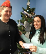 Janis Witchy, left, paymaster for the E.J. Brewer Detachment of the Marine Corps League, presents a check for $350 to Lindsay Winters Baker, director of development for Catholic Charities.