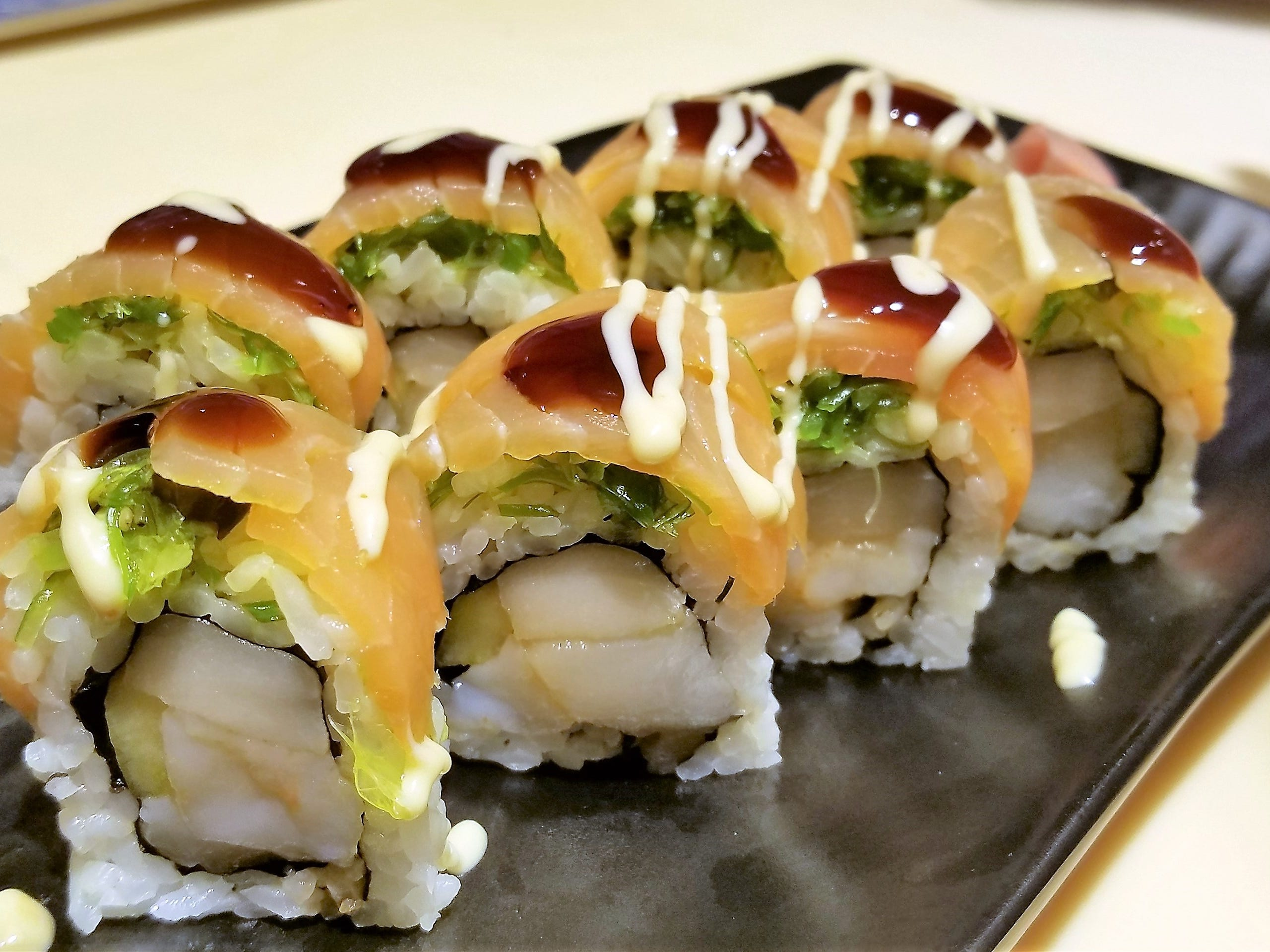 The hiyashi maki roll at Domo Sushi Bar and Ramen House, made with spicy scallops, albacore tuna and cucumber, topped with smoked salmon, seaweed salad, mayonnaise sauce and sweet soy sauce.