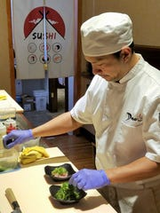 Martin Abadicio of Domo Sushi Bar and Ramen House assembles a Domo Salad and Seaweed Salad for guests.
