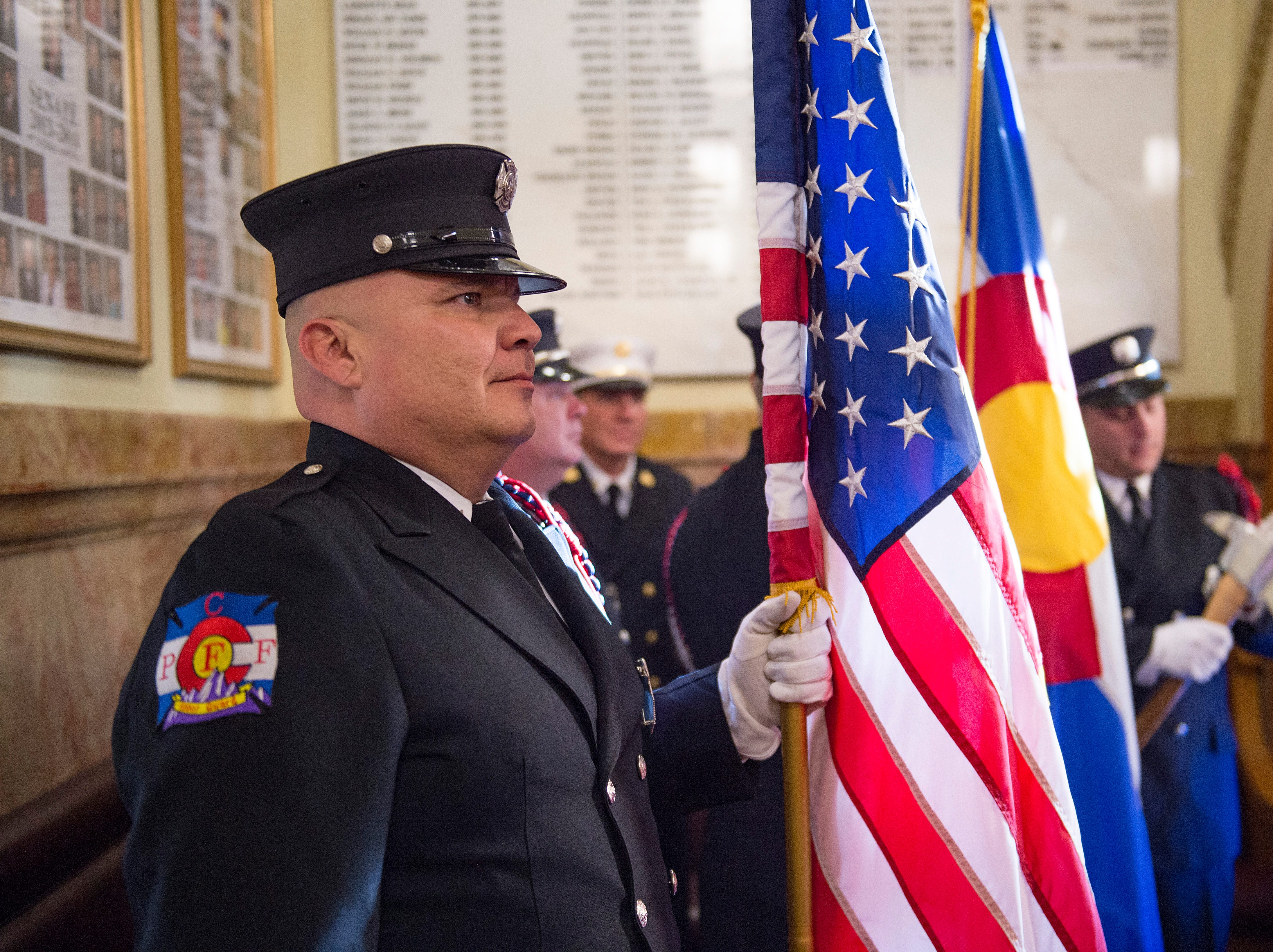 Joey Gutierrez with the City of Pueblo Fire Department stands with the United States flag before before entering the senate chambers as the 72nd General Assembly convenes at the Colorado State Capitol on Friday, January 4, 2019.