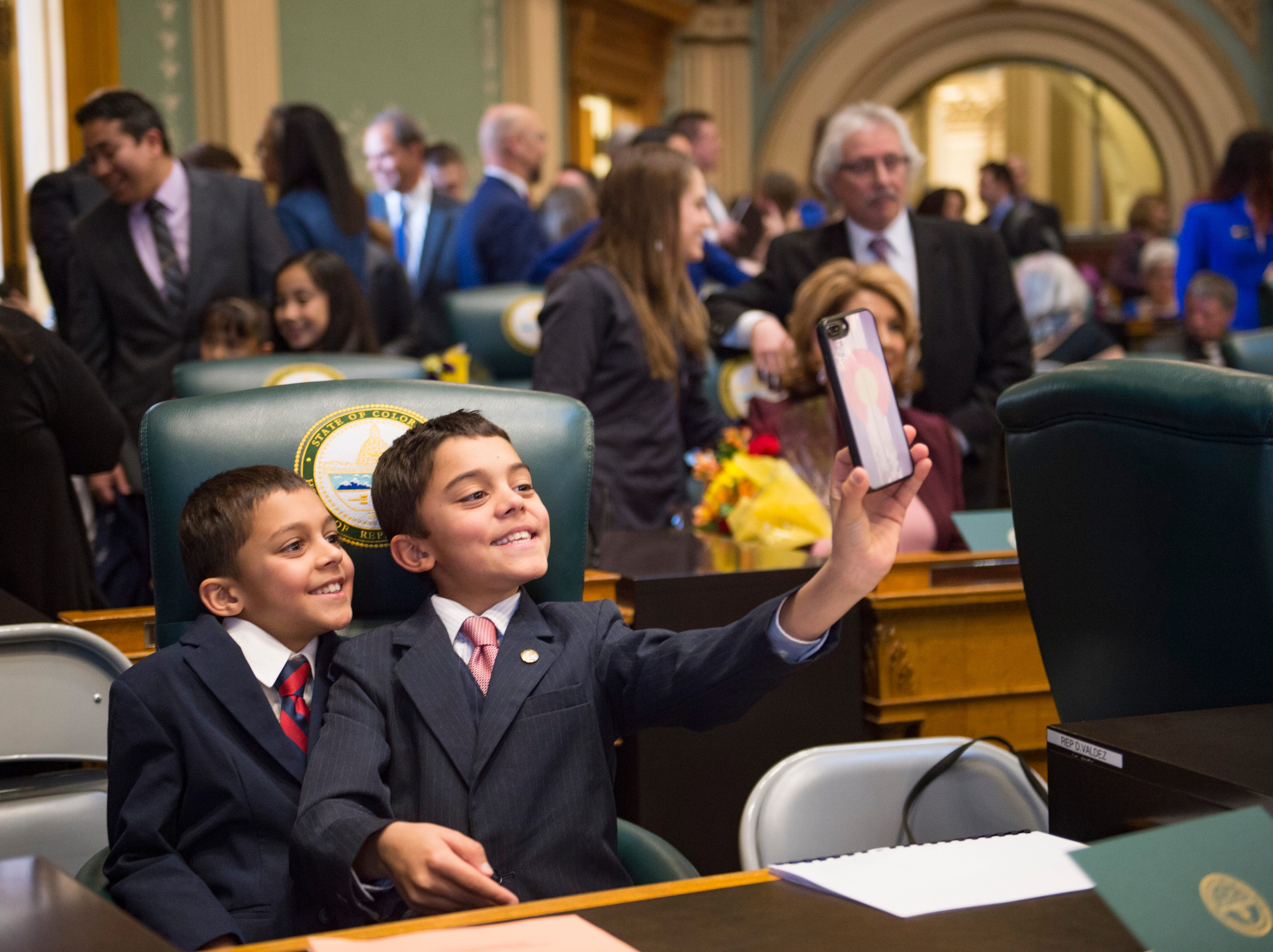 Ashwin Hansen, 10, and his brother Sachin, 12, take a photo at their father, Representative Chris Hansen's, desk as the 72nd General Assembly convenes at the Colorado State Capitol on Friday, January 4, 2019.