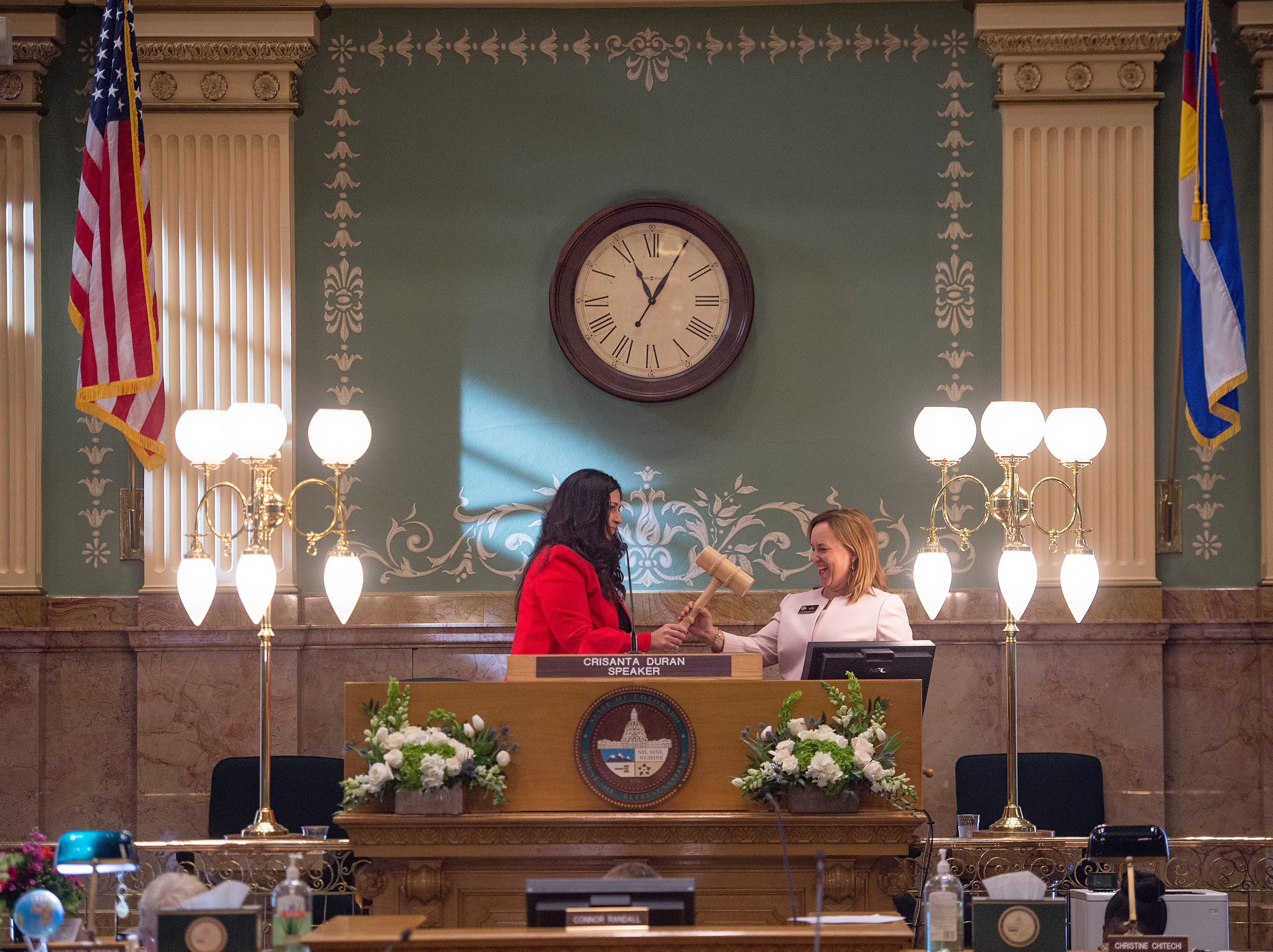 Crisanta Duran hands over a gavel to Speaker of the House KC Becker as the 72nd General Assembly convenes at the Colorado State Capitol on Friday, January 4, 2019.