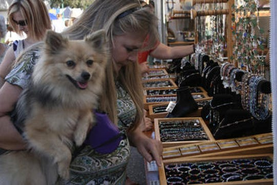 - Cape Coral resident Debbie Davis and her dog Bella check out some jewelry at last year's Cape Coral Festival of Arts and Music in 2012.
