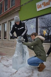 Jaden Stevenson and Katie Frank compete in the 2018 Fire and Ice carving competition in front of Get Real Cafe in Sturgeon Bay.