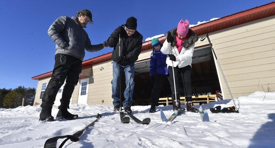 Tom and Barb Voegele assist Phil and Beth Thorngren of Rockford, Ill., with their cross-country skis last January for the Ski for Free program at Crossroads at Big Creek.