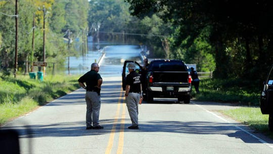 In this Wednesday, Sept. 19, 2018, file photo, responders congregate near where two people drowned the evening before when they were trapped in a Horry County Sheriff's transport van while crossing an overtopped bridge over the Little Pee Dee River on Highway 76, during rising floodwaters in the aftermath of Hurricane Florence in Marion County, S.C. Charges are expected to be filed Friday, Jan. 4, 2019, against two South Carolina law enforcement officers who were transporting two mental patients who drowned while locked in the back of a van during the hurricane.