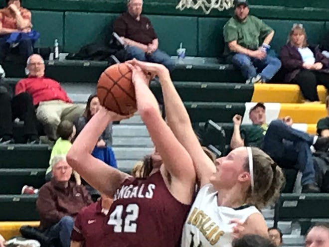 CMR's Allie Olsen (right) blocks a shot attempt by Helena's Jamie Pickens (42) in Thursday's nonconference game at the CMR Fieldhouse.