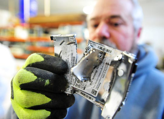 Ashley Ellmaker, a recycling tech with 406 Recycling, holds up a hard drive that has been partially shredded as part of the company's e-waste recycling service based in Montana City.