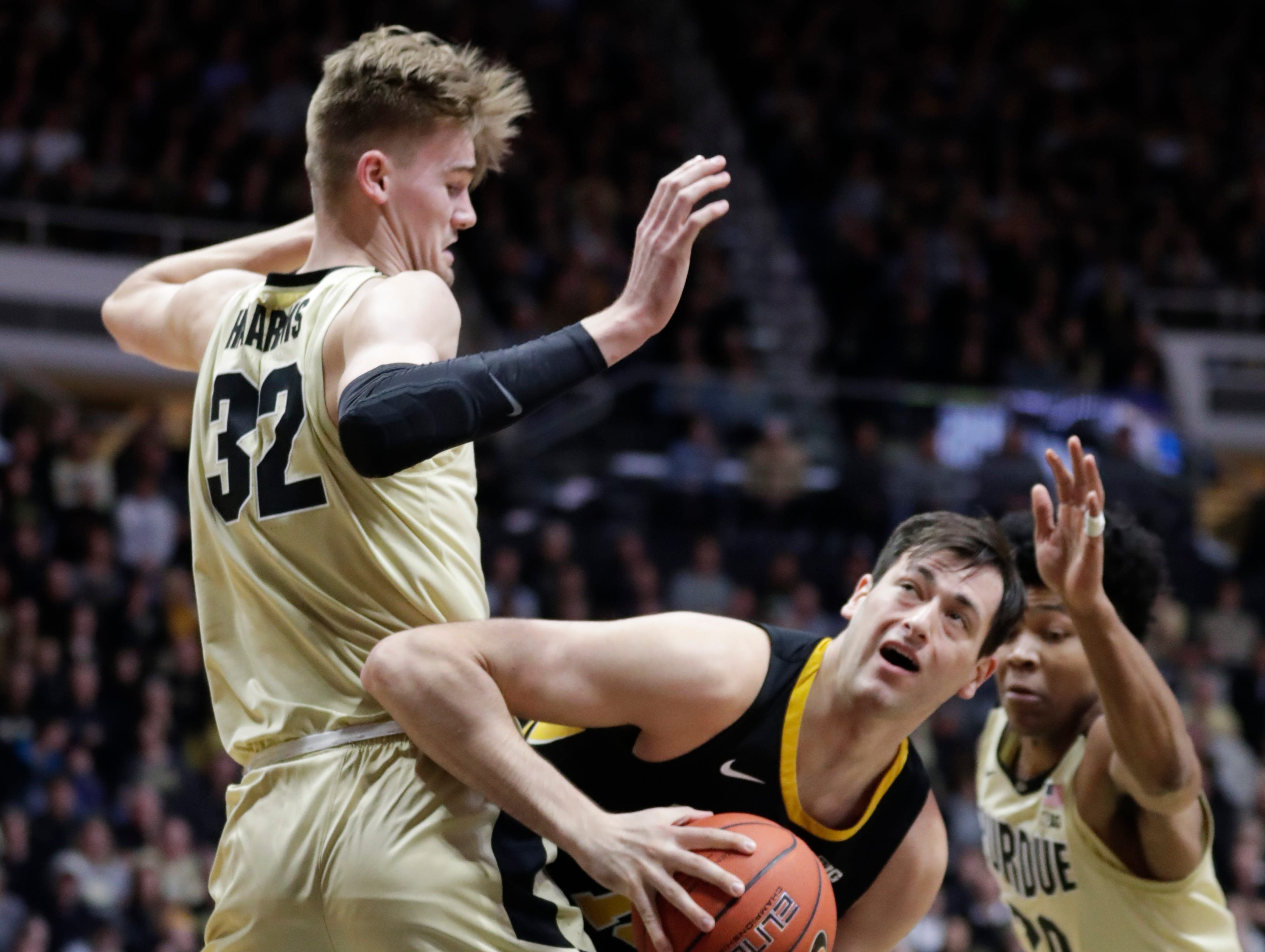Iowa forward Ryan Kriener (15) looks to shoot around Purdue center Matt Haarms (32) during the first half of an NCAA college basketball game in West Lafayette, Ind., Thursday, Jan. 3, 2019.