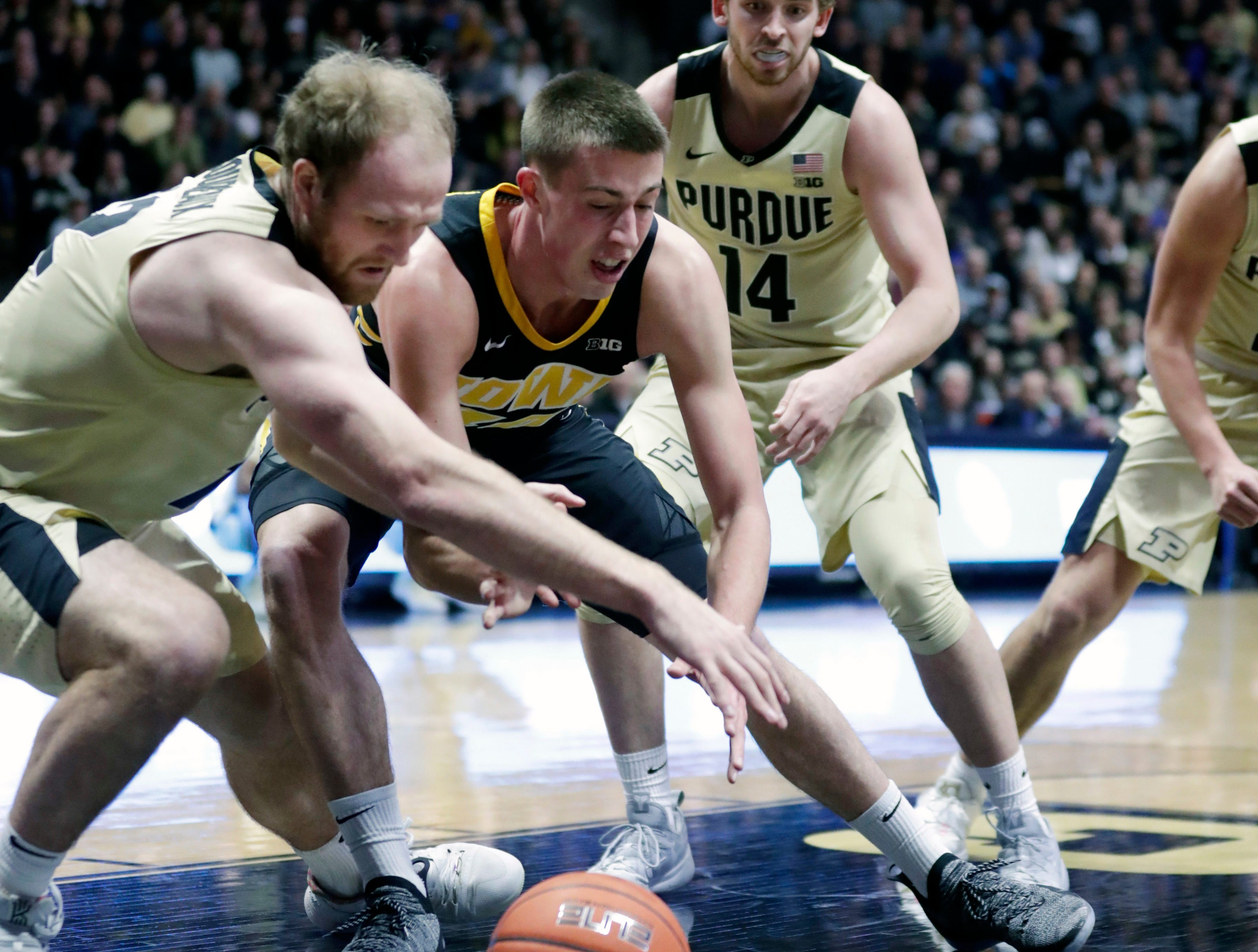 Iowa guard Joe Wieskamp (10) and Purdue forward Evan Boudreaux (12) battle for a loose ball during the first half of an NCAA college basketball game in West Lafayette, Ind., Thursday, Jan. 3, 2019.