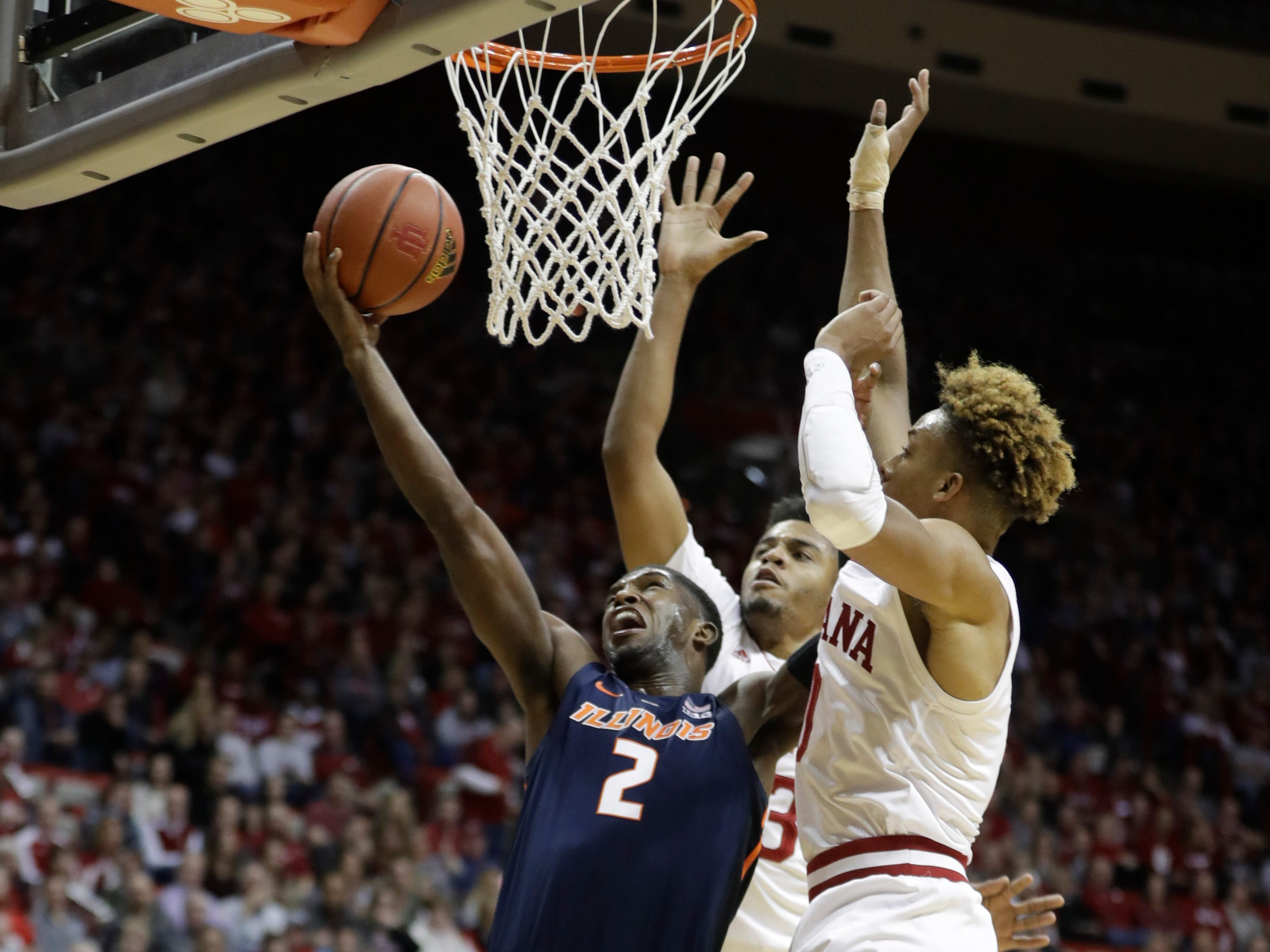 Illinois' Kipper Nichols (2) puts up a shot against Indiana's Juwan Morgan (13) and Romeo Langford (0) during the first half of an NCAA college basketball game Thursday, Jan. 3, 2019, in Bloomington, Ind.