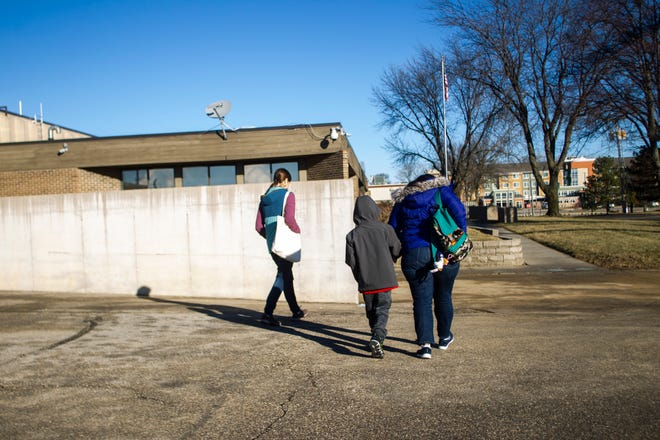 Catholic Worker House co-founder Emily Sinnwell, left, walks with Honduran asylum seeker Heybi Jakelin Torres-Toro while she holds hands with her son Josue Isaac Lopez-Torres, 10, before their first meeting with ICE on Friday, Jan. 4, 2019, at a Homeland Security Investigations office in Cedar Rapids.