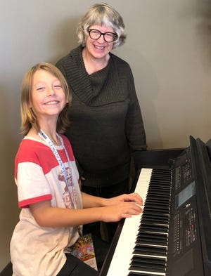 Henry Gilbertson-White and piano teacher Susan McGuire enjoy a moment of fun at the keyboard.