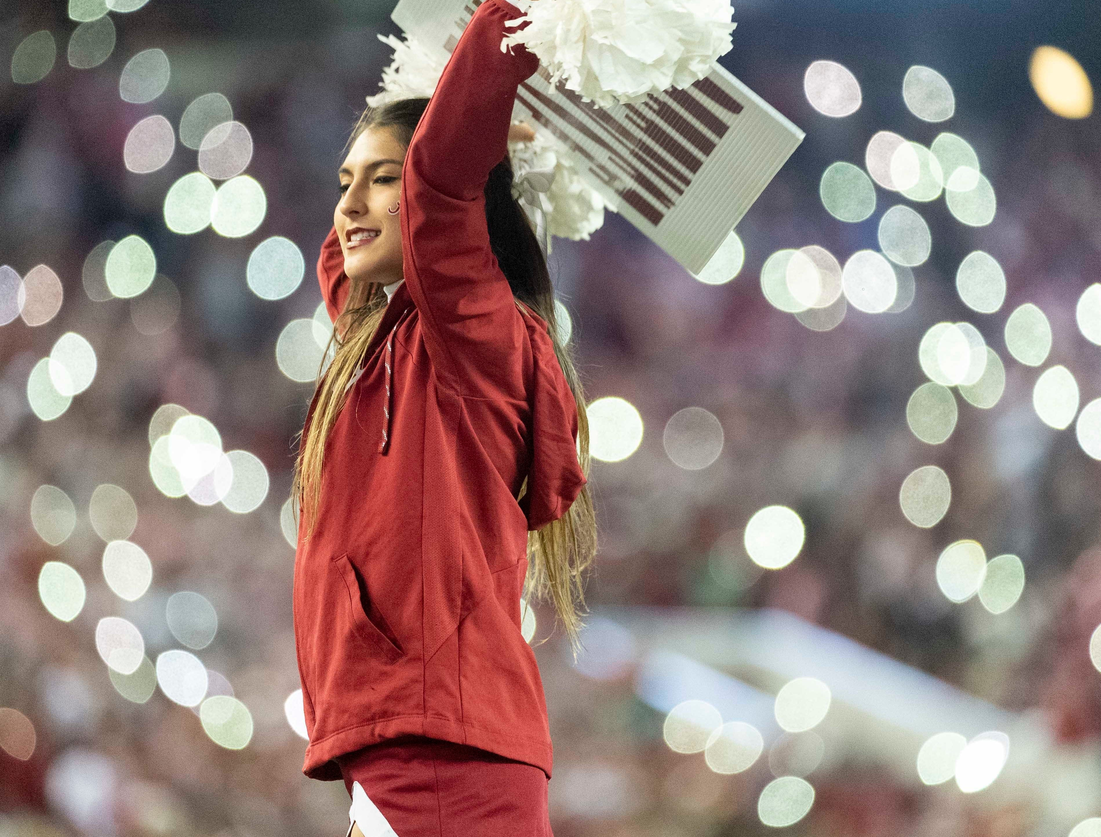 An Alabama cheerleader performs with cell-phone lights in the background during the second half of an NCAA college football game against Auburn, Saturday, Nov. 24, 2018, in Tuscaloosa, Ala. (AP Photo/Vasha Hunt)