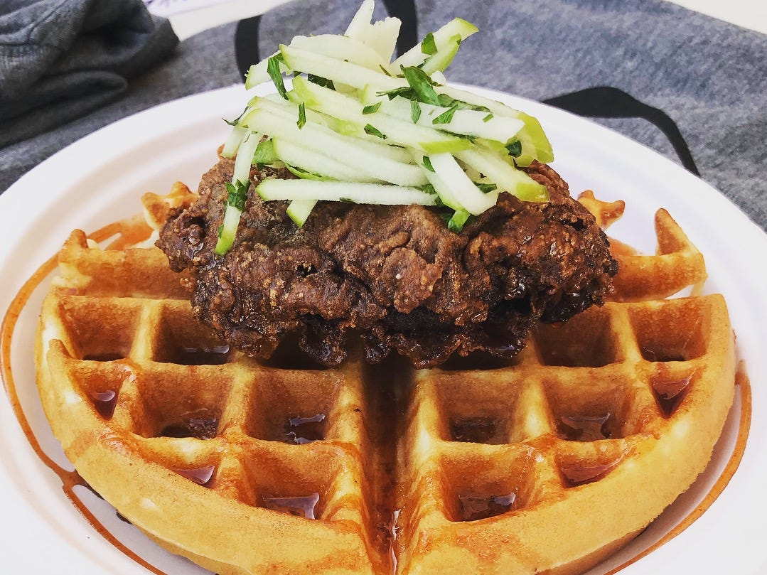 Ball's crispy chicken and waffles topped with apple slaw and maple cayenne syrup.