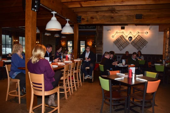 Members take a moment to post an update on social media during a Networking Today International meeting at Corner 16 Friday, Jan. 4.
