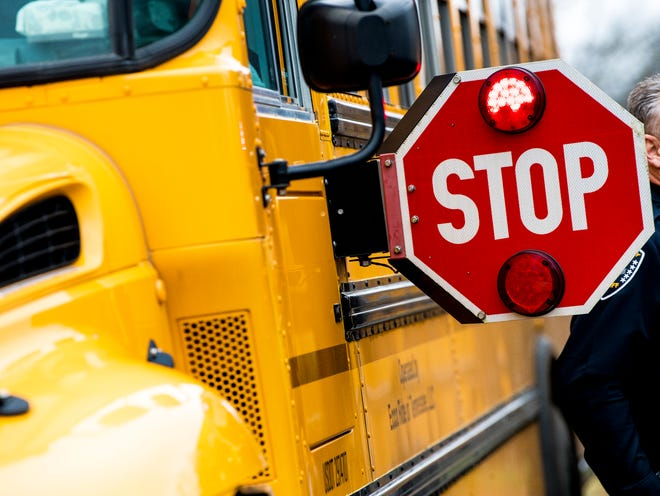 A Knox County school bus with its stop sign lit up at a press conference at Central High School on Friday, January 4, 2019. Local law enforcement will be cracking down on motorists who fail to stop for school buses.